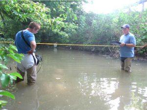 Ann McGhee (left) and Oscar Osario measuring the velocity of Ellejoy Creek.